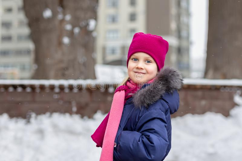 Portrait of happy adorable child laughing on city street during snowfall. Cute little caucasian girl in knitted hat and scarf and stock photo
