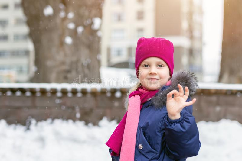 Portrait of happy adorable child showing OK sigh. Cute little caucasian girl in knitted hat and scarf and dawn jacket having fun stock images