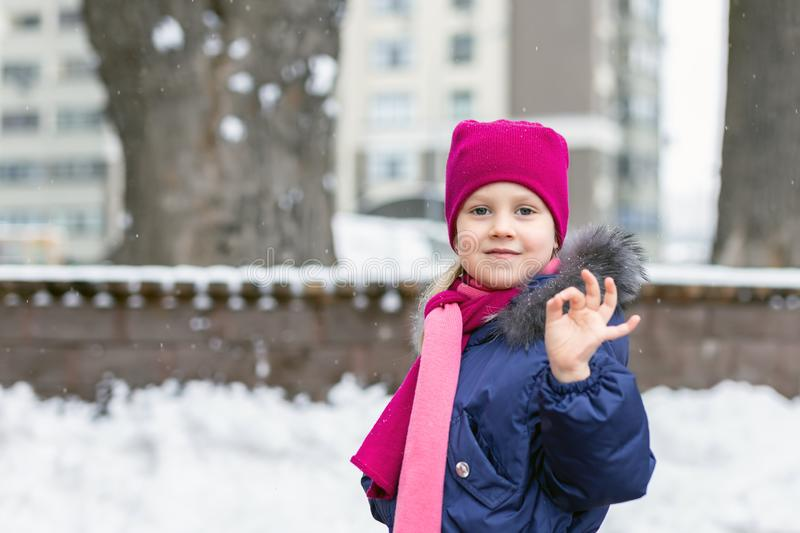 Portrait of happy adorable child showing OK sigh. Cute little caucasian girl in knitted hat and scarf and dawn jacket having fun. Playing outdoor in winter stock photos