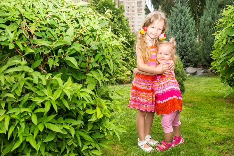 Portrait of happy adorable two sisters children girls outdoor. Cute little kid in summer day stock photos