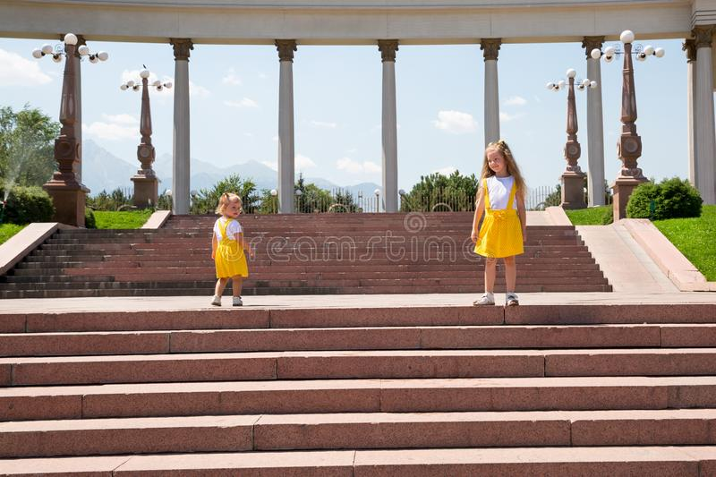 Portrait of happy adorable two sisters children girls outdoor. Cute little kid in summer day. Portrait of happy adorable two sisters children girls outdoor. Cute stock image
