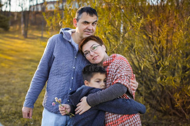 Portrait of happy adult married couple with son at sunset in the park in selective focus stock images