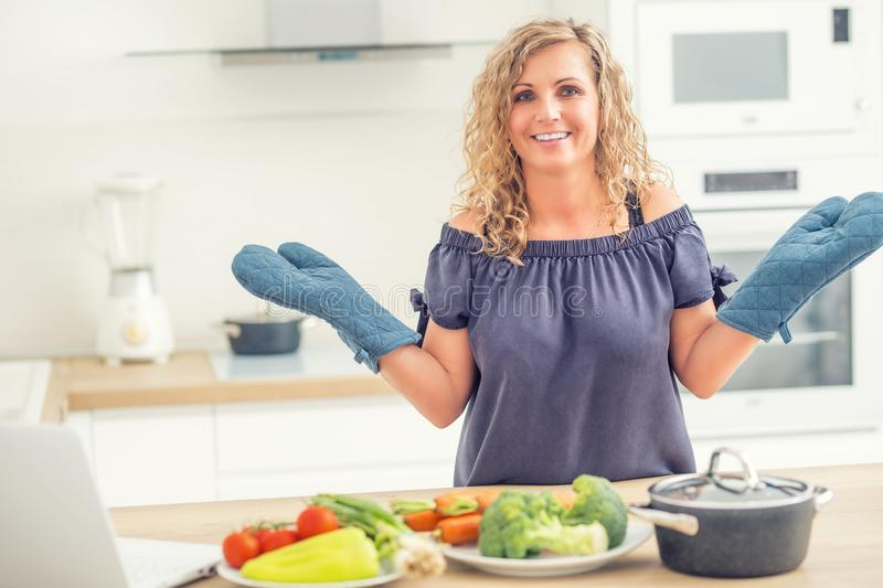 Portrait of happy adult woman in her modern kitchen with pot and vegetables. Young, cooking, healthy, home, food, female, caucasian, beautiful, diet, person royalty free stock images