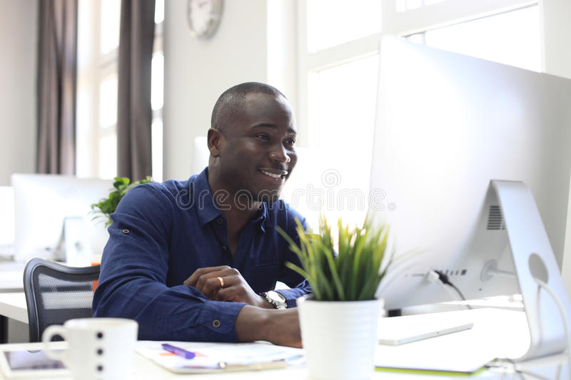 Portrait of a happy African American entrepreneur displaying computer in office. royalty free stock images