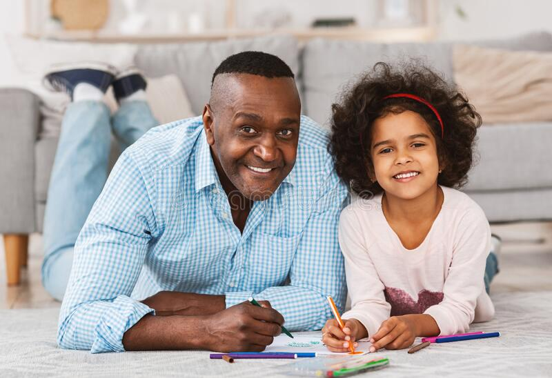 Portrait of happy African American family drawing on floor at home. Creative quarantine pastimes. Concept royalty free stock photography
