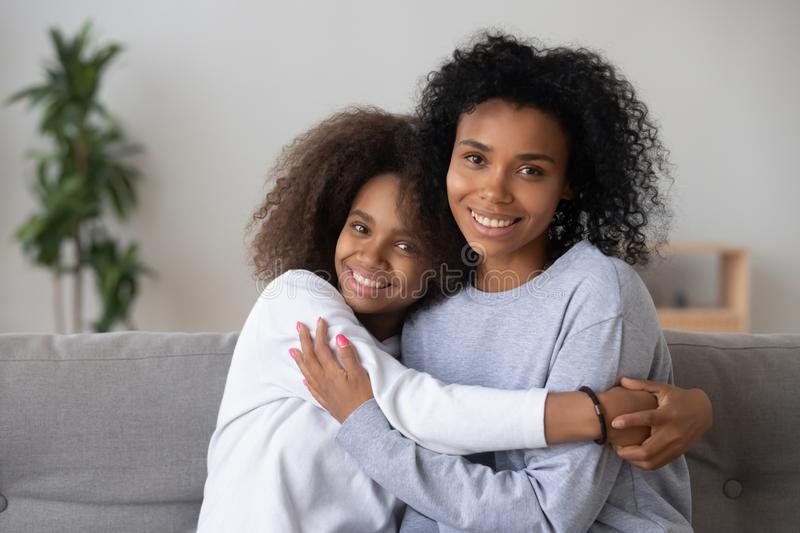Portrait of smiling black mom and daughter hugging on couch royalty free stock photography