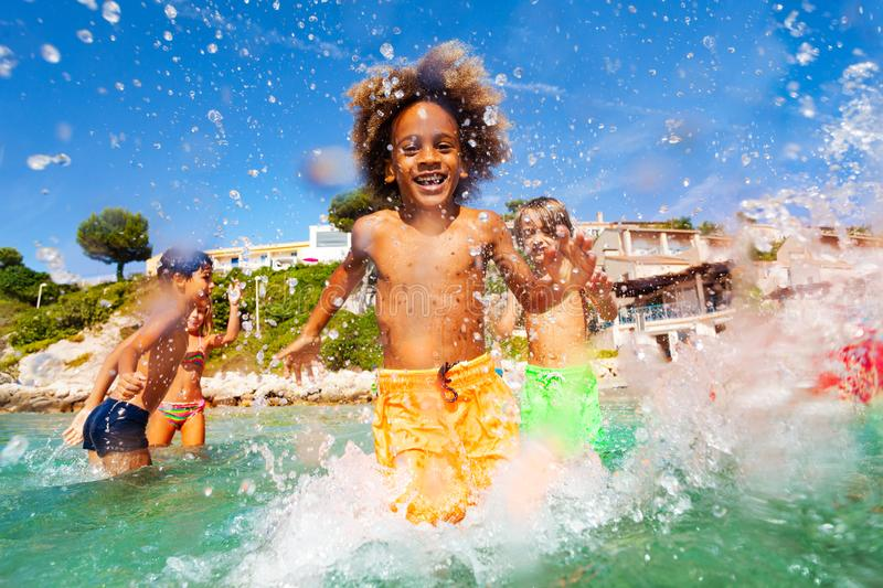 African boy playing with friends in shallow water stock image