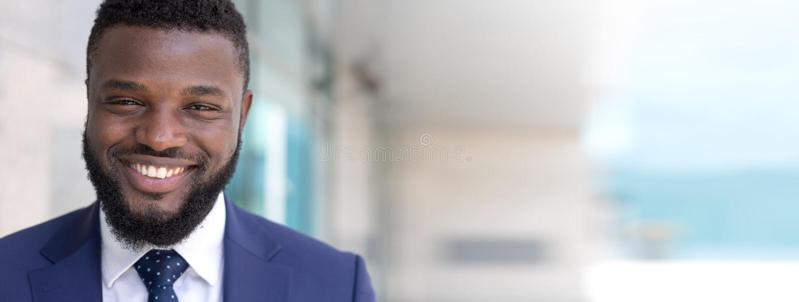 Portrait of happy african businessman looking at camera outdoors. Long copy space stock image
