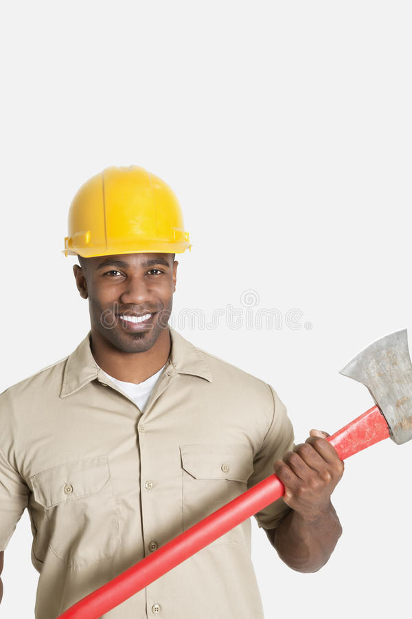 Portrait of happy African male construction worker holding axe over gray background royalty free stock images