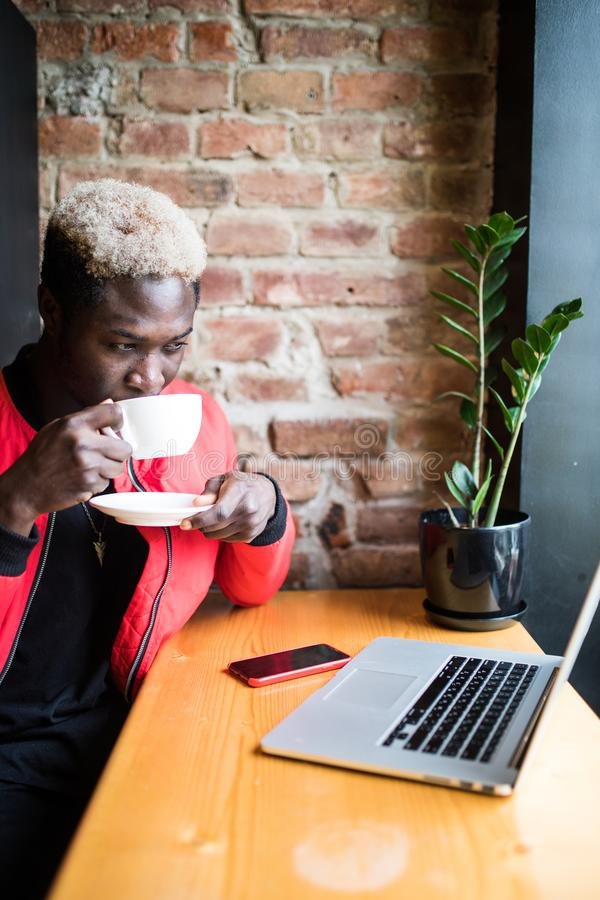 Portrait of a happy afro american man drinking morning coffee at cafe royalty free stock photo