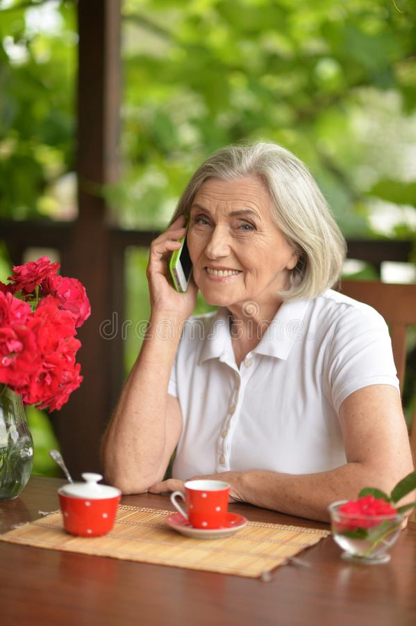 Portrait of a happy aged woman talking on smartphone stock images