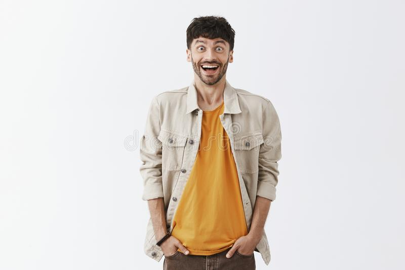 Portrait of happy amazed good-looking male with dark hair and beard with broad astonished smile holding hands in pockets royalty free stock photos
