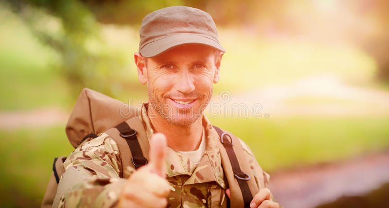 Portrait of happy army man with thumbs up. Standing in park stock photo