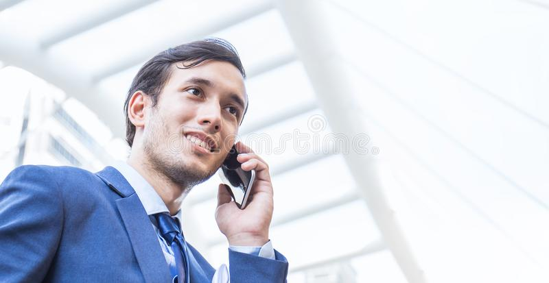Portrait of happy asian businessman standing outside using mobile phone stock photography
