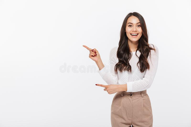 Portrait of a happy asian businesswoman pointing finger away royalty free stock images