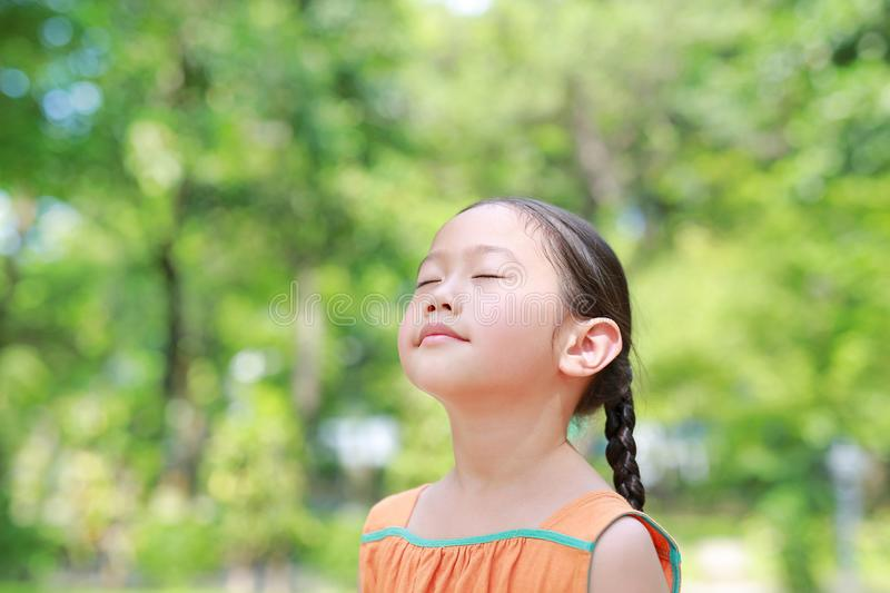 Portrait of happy Asian child close their eyes in garden with Breathe fresh air from nature. Close up kid girl relax in green park royalty free stock photography