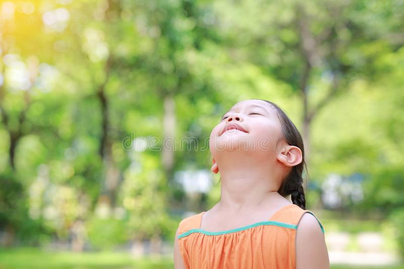 Portrait of happy Asian child close their eyes in garden with Breathe fresh air from nature. Close up kid girl relax in green park. For good health royalty free stock images
