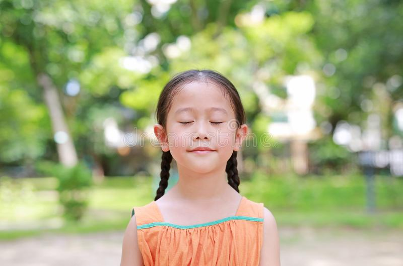 Portrait of happy Asian child close their eyes in garden with Breathe fresh air from nature. Close up kid girl relax in green park stock images