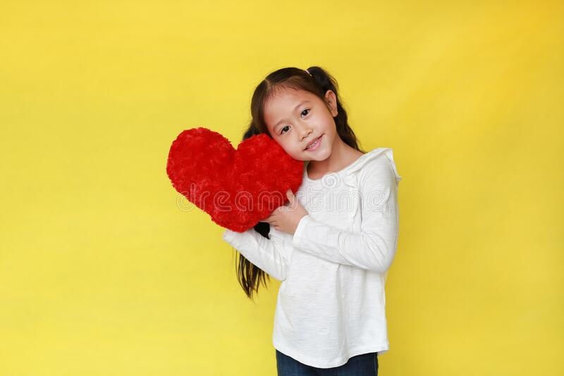 Portrait of happy asian child girl holding a fluffy red heart for you isolated on yellow background royalty free stock photography