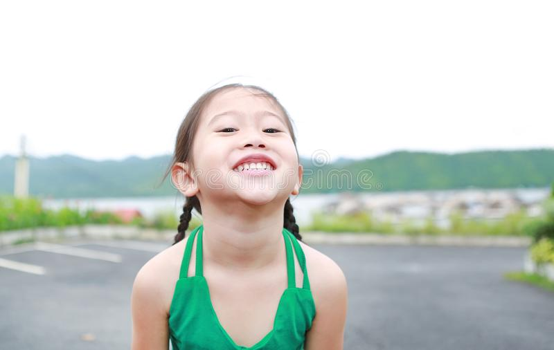 Portrait of happy Asian child girl relaxes in hillside royalty free stock photography