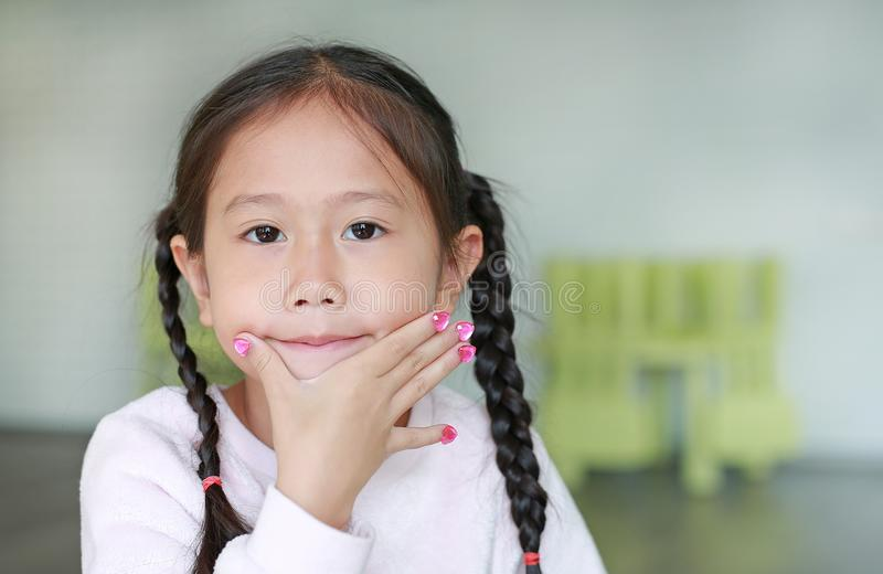 Portrait of Happy asian child girl showing her nails with fashion jewels stock image