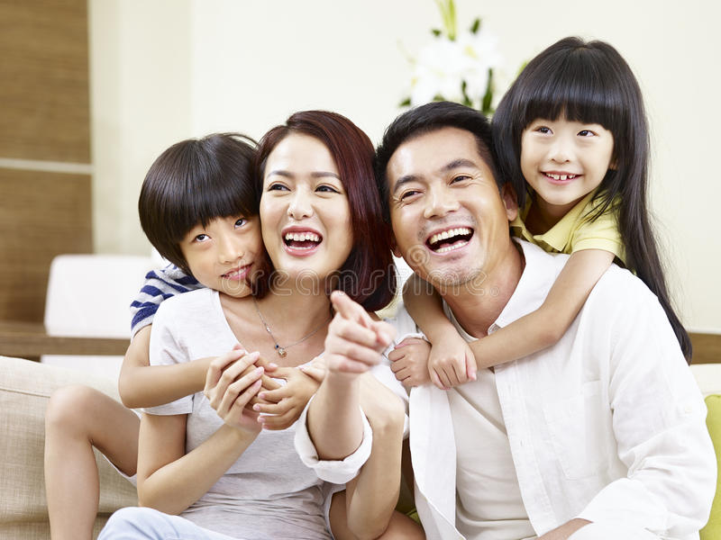 Portrait of happy asian family. Portrait of a happy asian family sitting on couch at home, smiling and laughing royalty free stock images