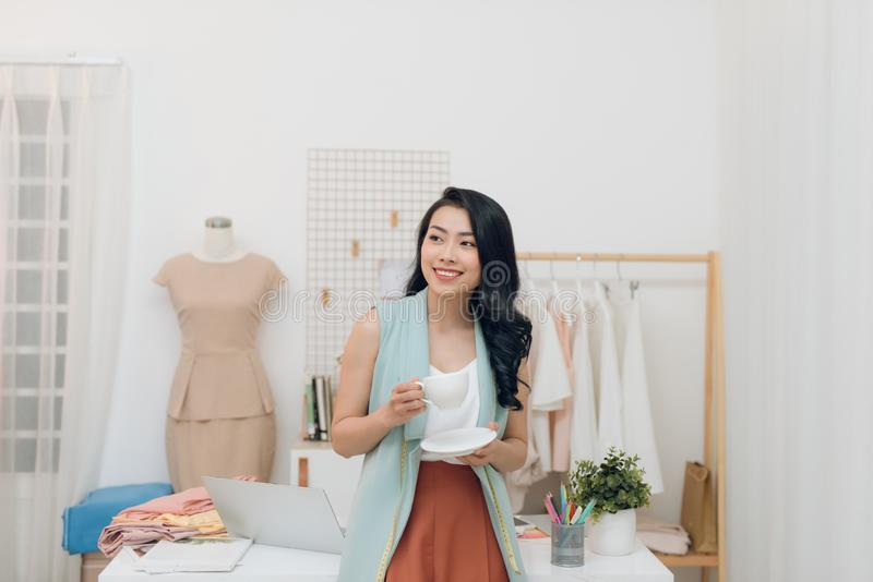 Portrait of happy Asian fashion designer businesswoman at studio. Smiling, standing, looking at camera stock photo