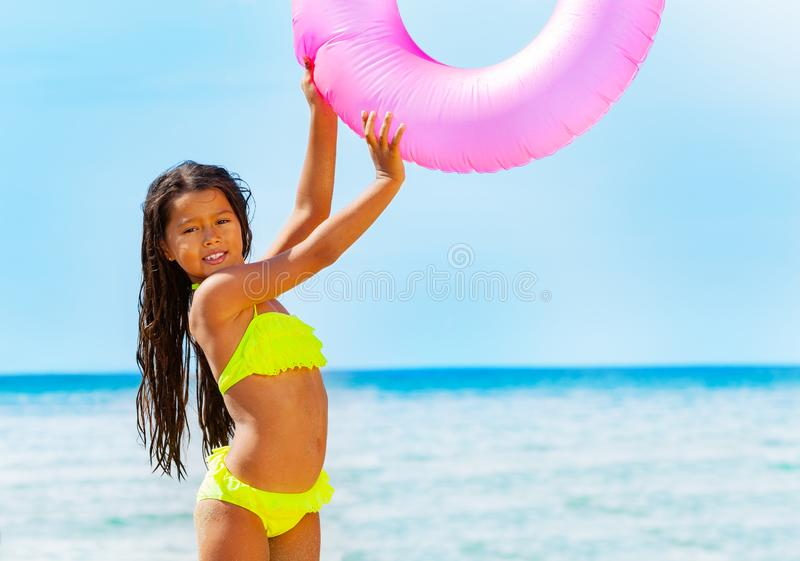 Asian girl with swim tube playing on the beach. Portrait of happy Asian girl in bikini holding big pink swim tube while playing on the beach in summer stock image