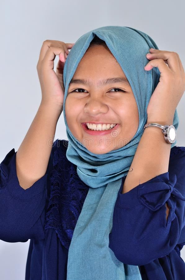 Portrait of happy asian girl wearing blue hijab smiling at you and touching her haed stock image