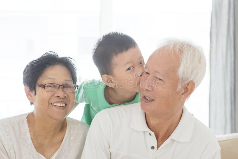 Grandchild kissing grandparents royalty free stock image