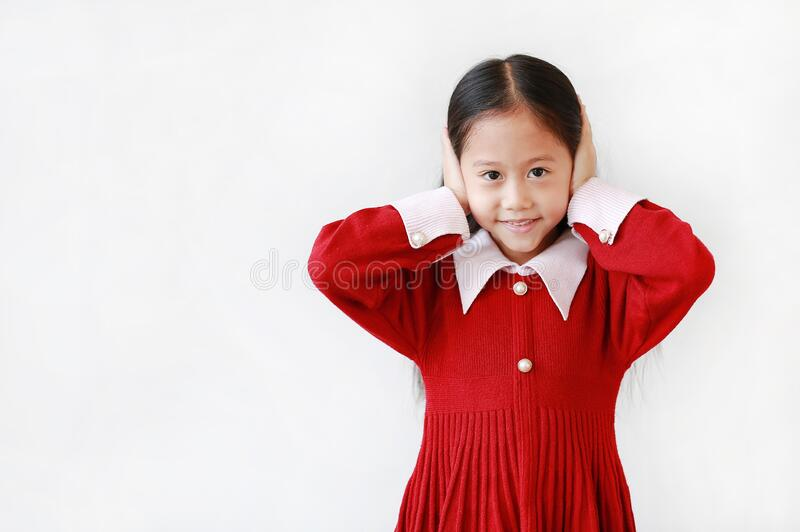 Portrait of happy asian little child girl covering ears by hands not to hear isolated over white background with copy space stock images
