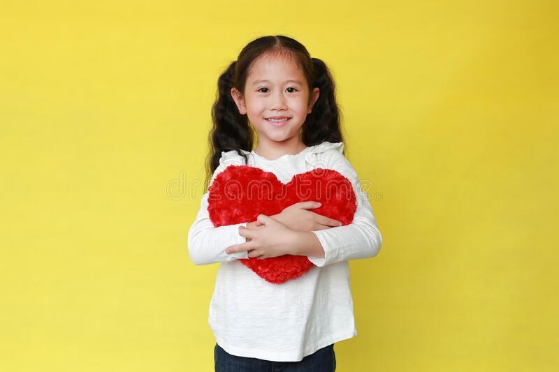 Portrait of happy asian little child girl cuddle a fluffy red heart with looking camera isolated on yellow background royalty free stock image