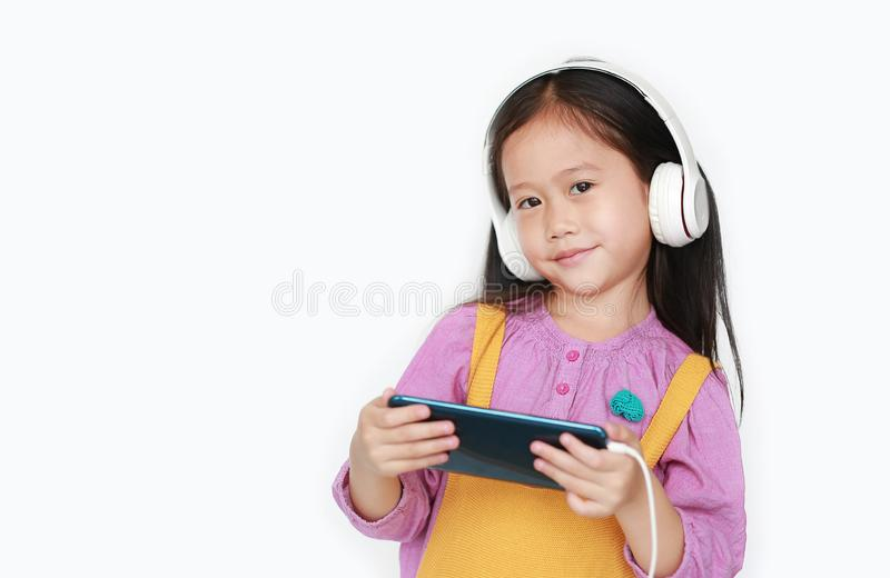 Portrait of happy Asian little girl enjoys listening music with headphones by smartphone isolated over white background.  stock photos