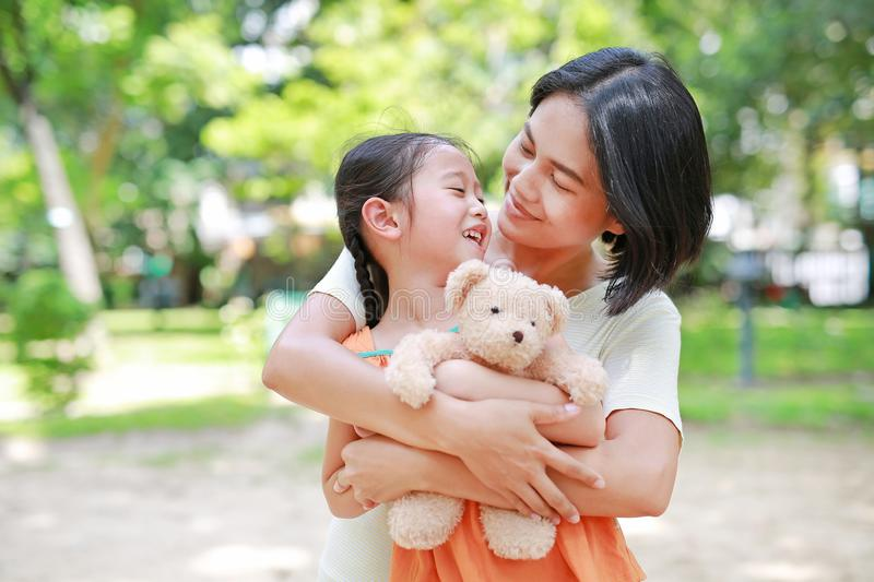 Portrait of happy Asian mother cuddle daughter and hugging teddy bear doll in the garden. Mom and child girl with love and royalty free stock image