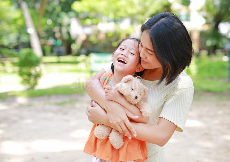 Portrait of happy Asian mother cuddle daughter and hugging teddy bear doll in the garden. Mom and child girl with love and. Relationship concept stock photo