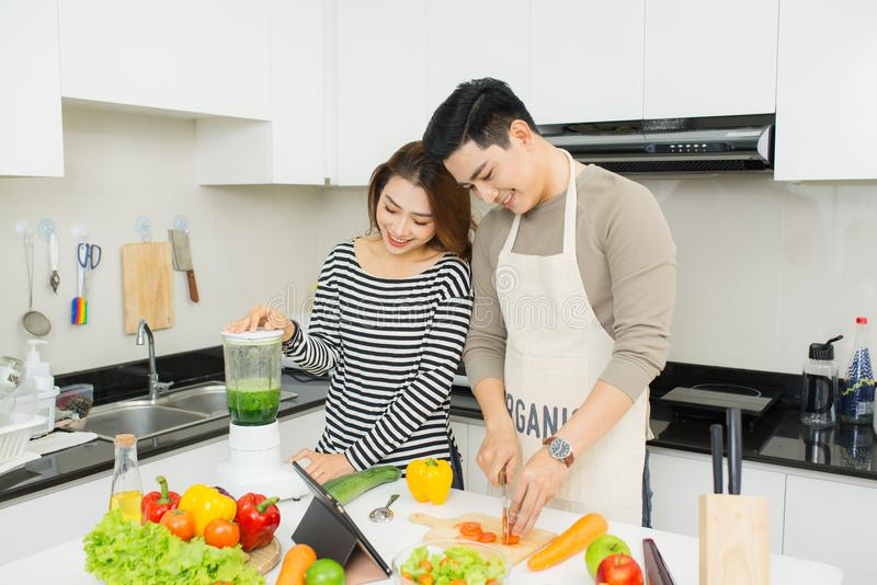Portrait of happy asian young couple cooking together in the kit stock images