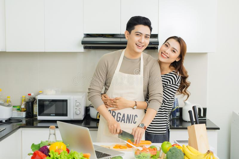 Portrait of happy asian young couple cooking together in the kit stock image