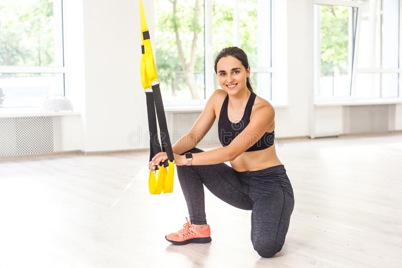 Portrait of happy attractive young sports woman is doing TRX training, sitting on the floor and holding fitness straps while stock photo