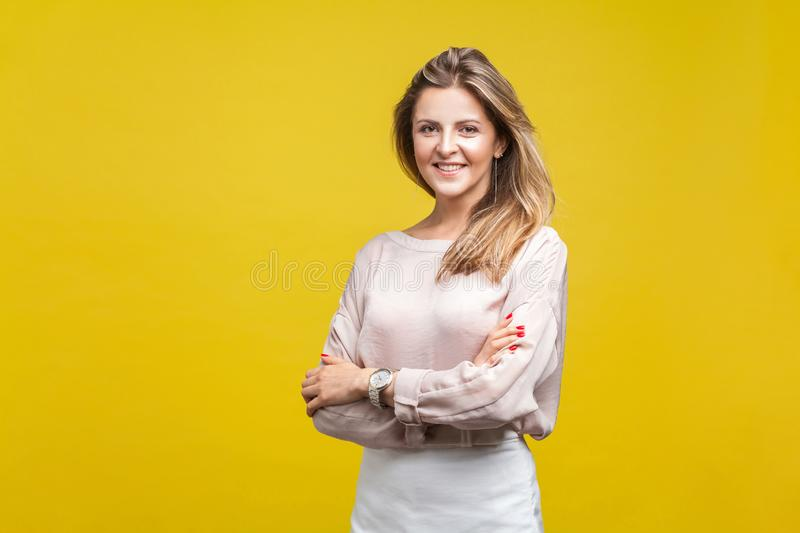 Portrait of happy attractive young woman with fair hair in casual beige blouse, isolated on yellow background. Portrait of happy attractive young woman with fair stock images