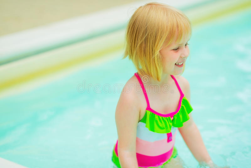 Portrait of happy baby girl in swimming pool. Portrait of happy baby girl in swimsuit in swimming pool royalty free stock photos
