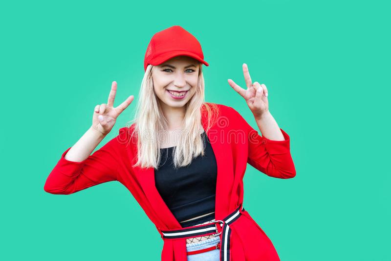 Portrait of happy beautiful blond young hipster style woman in red blouse and cap, standing with victory sign and looking at. Camera with toothy smile. indoor royalty free stock photography