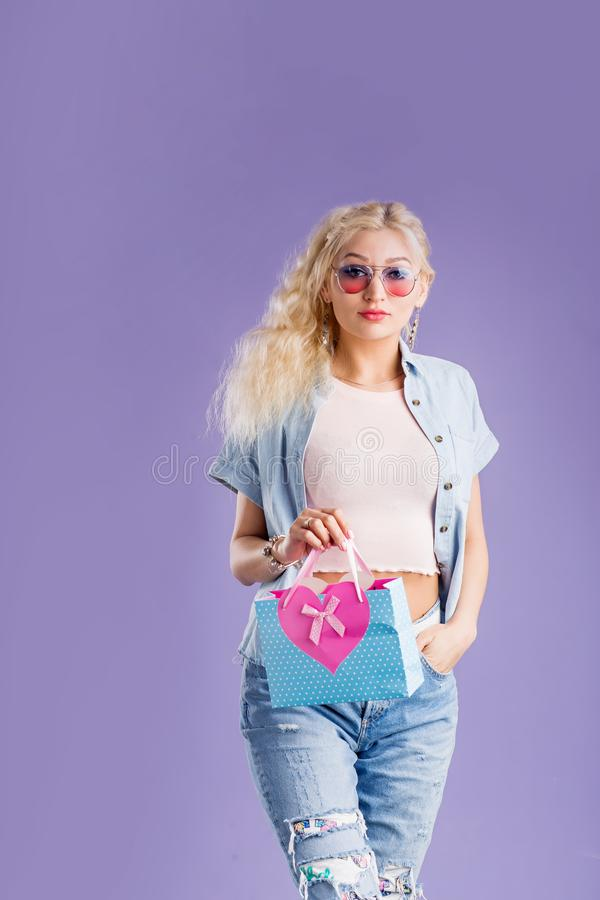 Portrait of young happy woman with shopping bag isolated over violet background royalty free stock photo