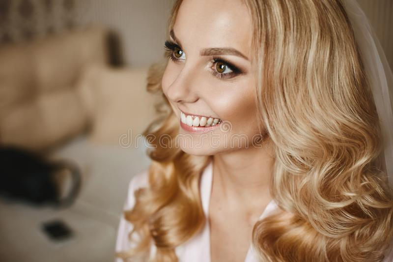 Portrait of happy beautiful blonde model girl with bright makeup and shiny smile stock image