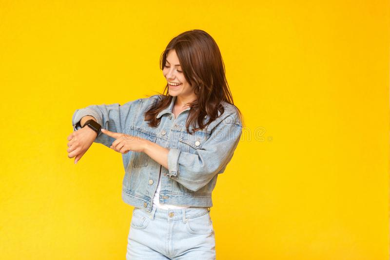 Portrait of happy beautiful brunette young woman in denim casual style standing, toothy smiling, touching and checking her smart stock image