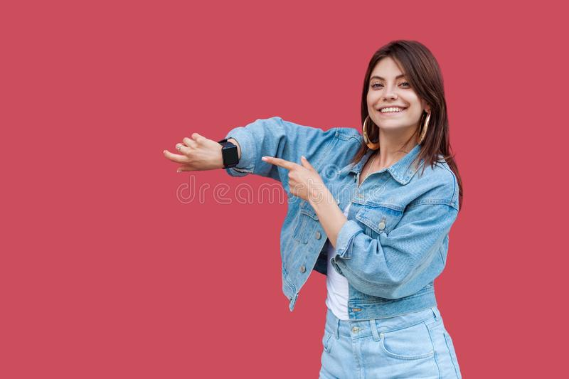 Portrait of happy beautiful brunette young woman with makeup in denim casual style standing showing and pointing at her smart royalty free stock photography