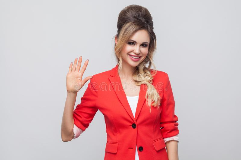 Portrait of happy beautiful business lady with hairstyle and makeup in red fancy blazer, standing and looking at camera with. Greeting gesture. indoor studio royalty free stock photography
