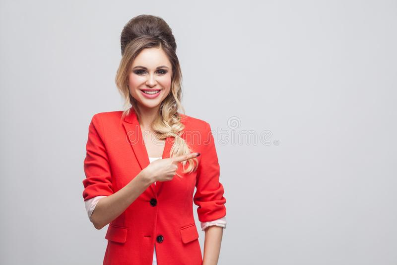 Portrait of happy beautiful business lady with hairstyle, makeup in red fancy blazer, standing, looking at camera and pointing at. Copyspace with toothy smile royalty free stock photos
