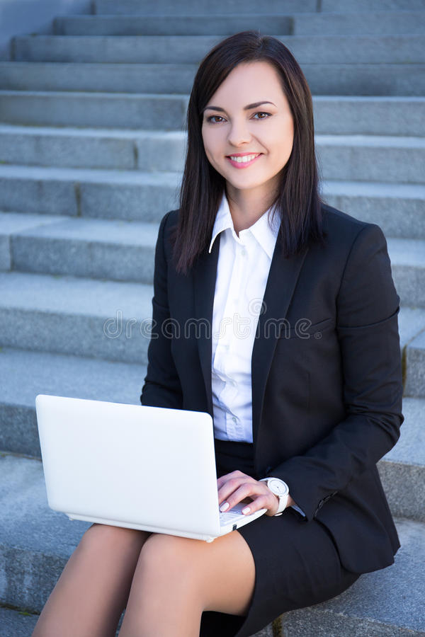 Portrait of happy beautiful business woman sitting on stairs and stock photos