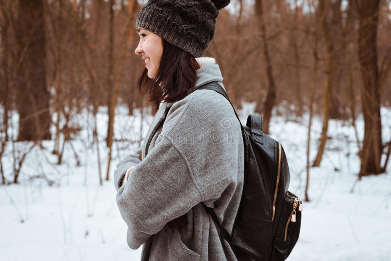 Portrait of a happy beautiful girl with brown hair in the winter forest dressed in a hipster style, lifestyle royalty free stock photos