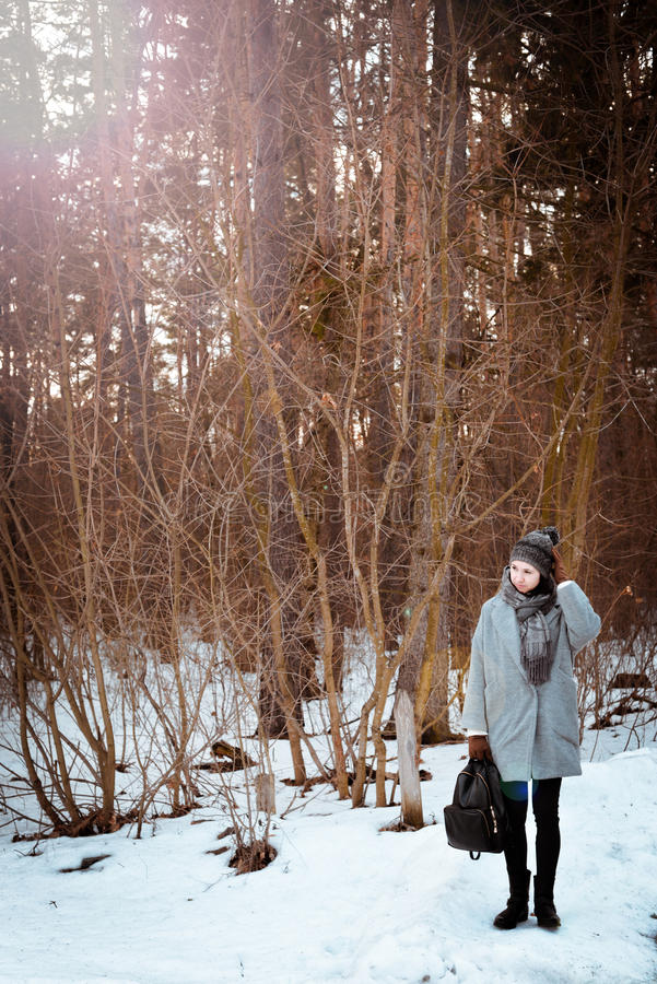 Portrait of a happy beautiful girl with brown hair in the winter forest dressed in a hipster style, lifestyle stock image